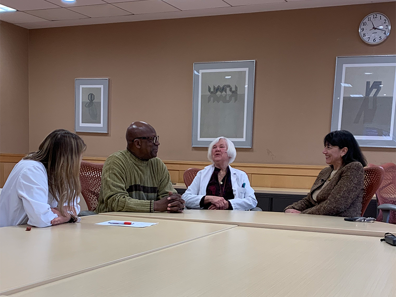 Dr. Bertagnolli and two other doctors sit together at a table with a patient