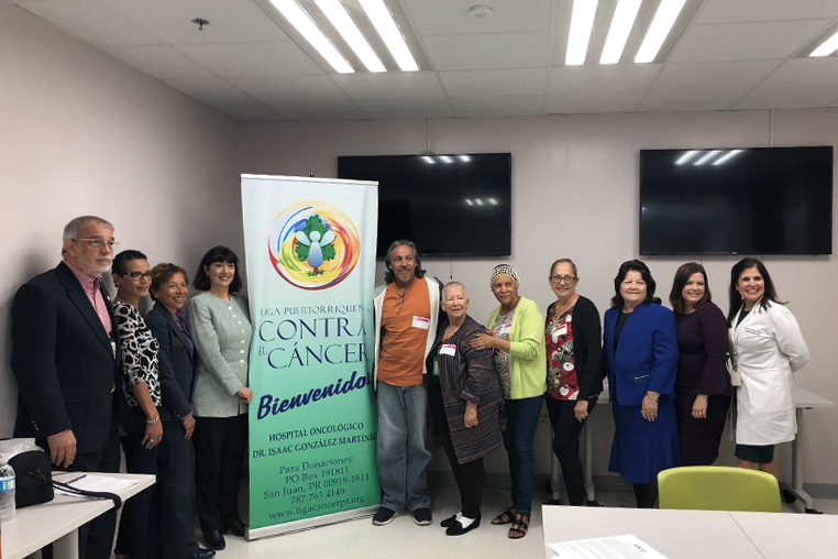 Photo of community members standing around a sign that says contra cáncer and bienvenido