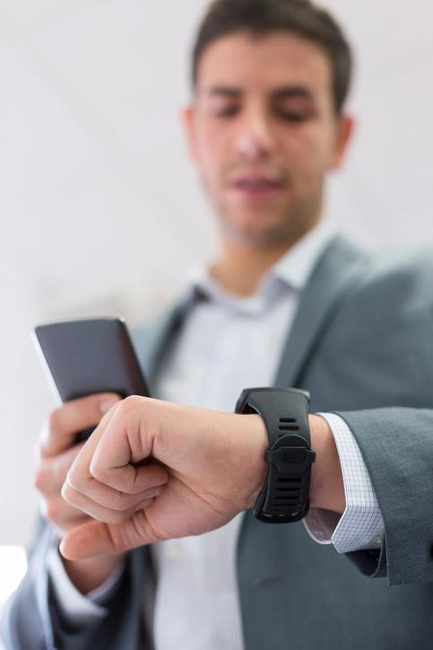 Businessman looking at watch and phone